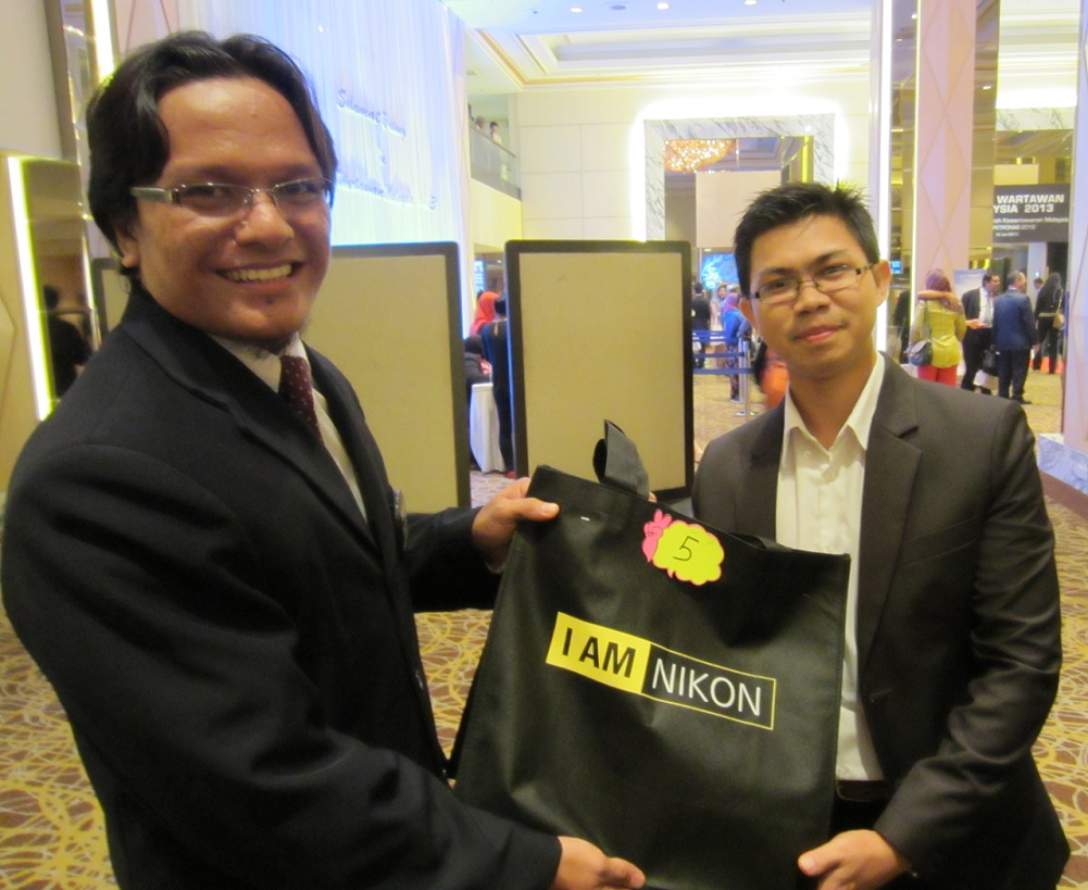Tuah menyebelahi Encik Husli (JabatanPenerangan Malaysia) yang membawa hadiah tajaan daripada NIKON (M) Sdn Bhd berupa kamera NIKON COOLPIX S100.