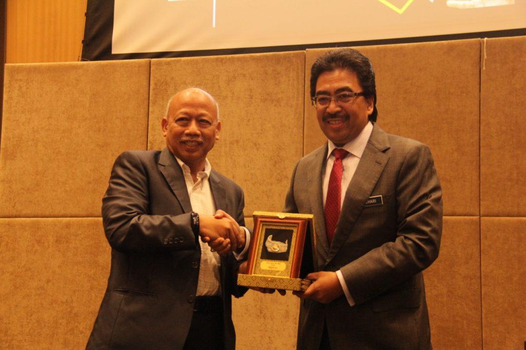 Datuk Dr. Chamil Wariya, Ketua Pegawai Eksekutif MPI menyampaikan cenderahati sebagai tanda penghargaan kepada Datuk Seri Johari Abdul Ghani, Menteri Kewangan II.